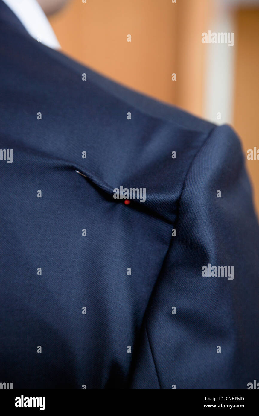 Detail of a pin in the shoulder of a suit jacket - Stock Image