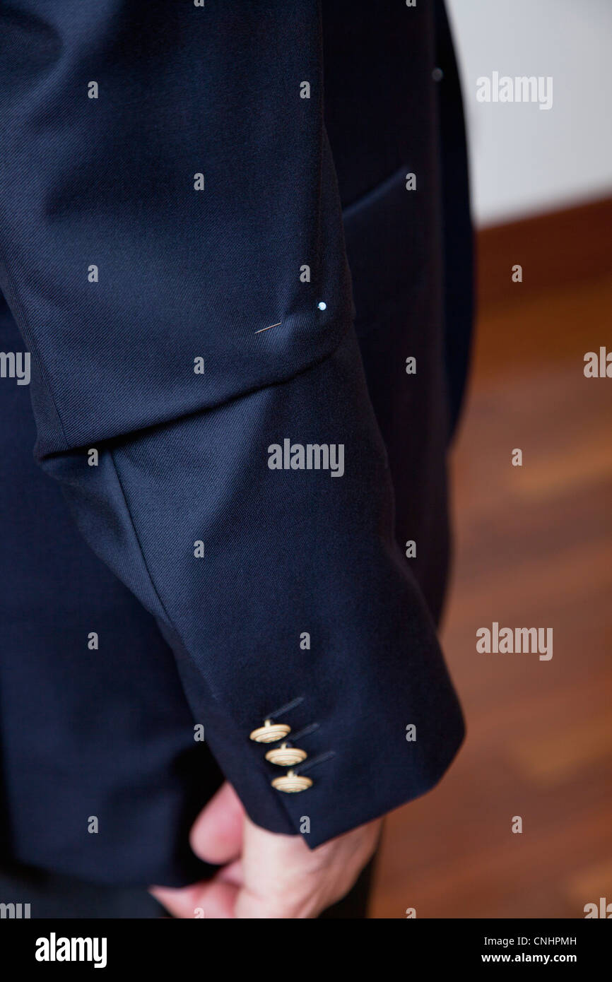 Detail of a pin in the sleeve of a man's suit jacket - Stock Image