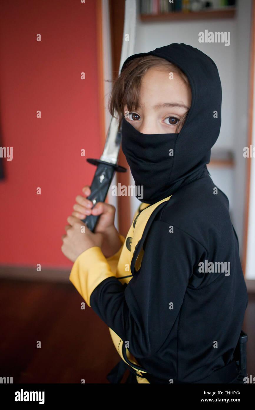A boy dressed in a ninja costume holding a samurai sword Stock Photo