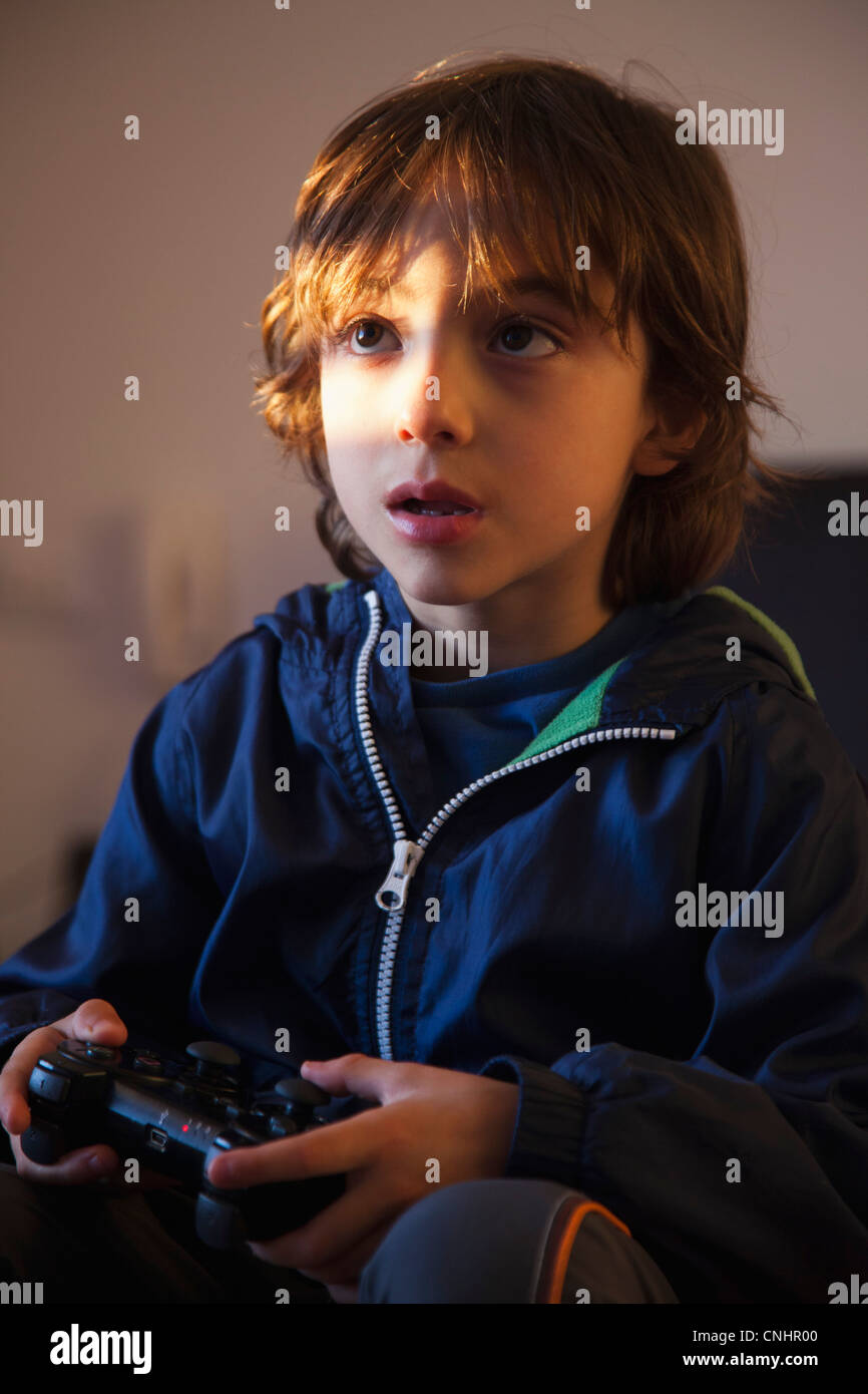A young boy holding a video game controller looking concentrated - Stock Image