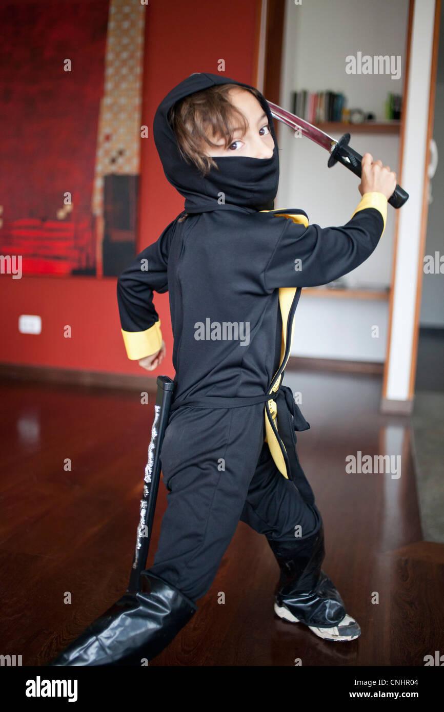 A boy dressed in a ninja costume swinging a samurai sword & A boy dressed in a ninja costume swinging a samurai sword Stock ...