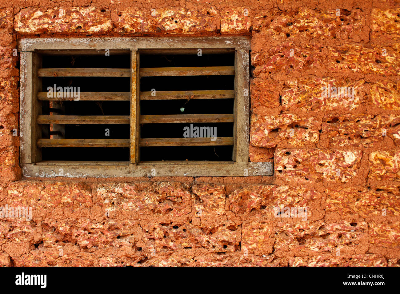 Wooden window on a mud-brick wall - Stock Image