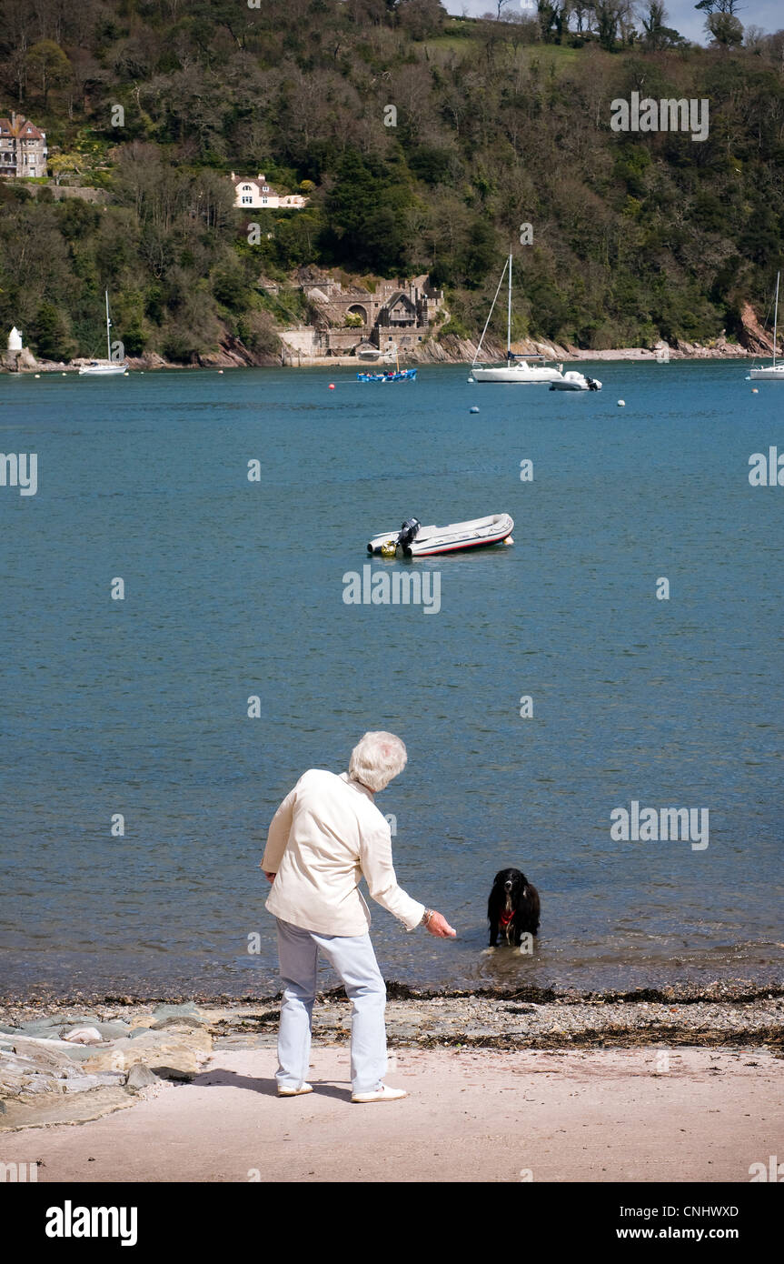 man skimming stones at warfleet on the river Dart watched by his dog,mans best friend,man skimming stones,dapper,natty - Stock Image