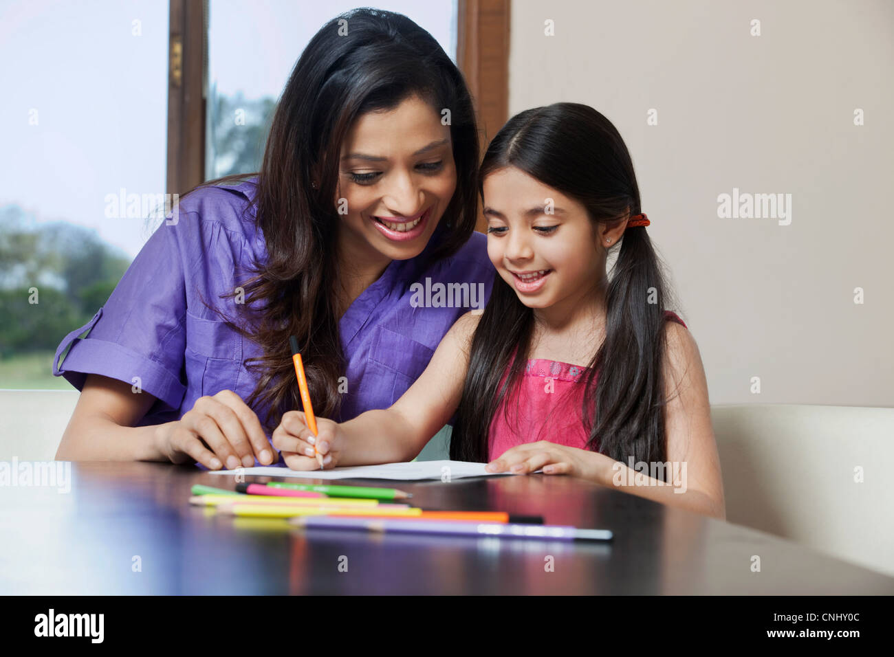 Girl writing while her mother looks on - Stock Image
