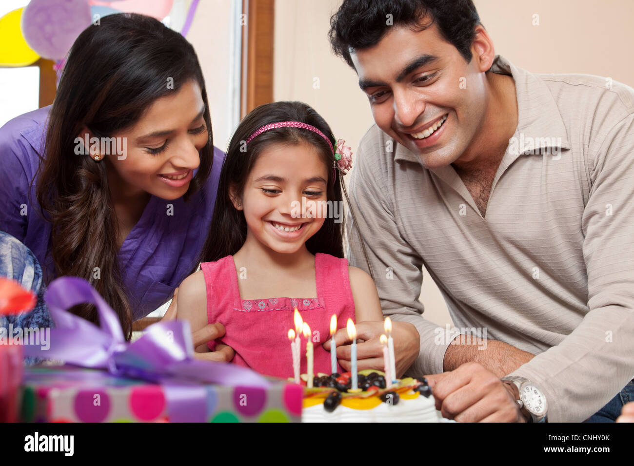 Girl celebrating her birthday with parents Stock Photo