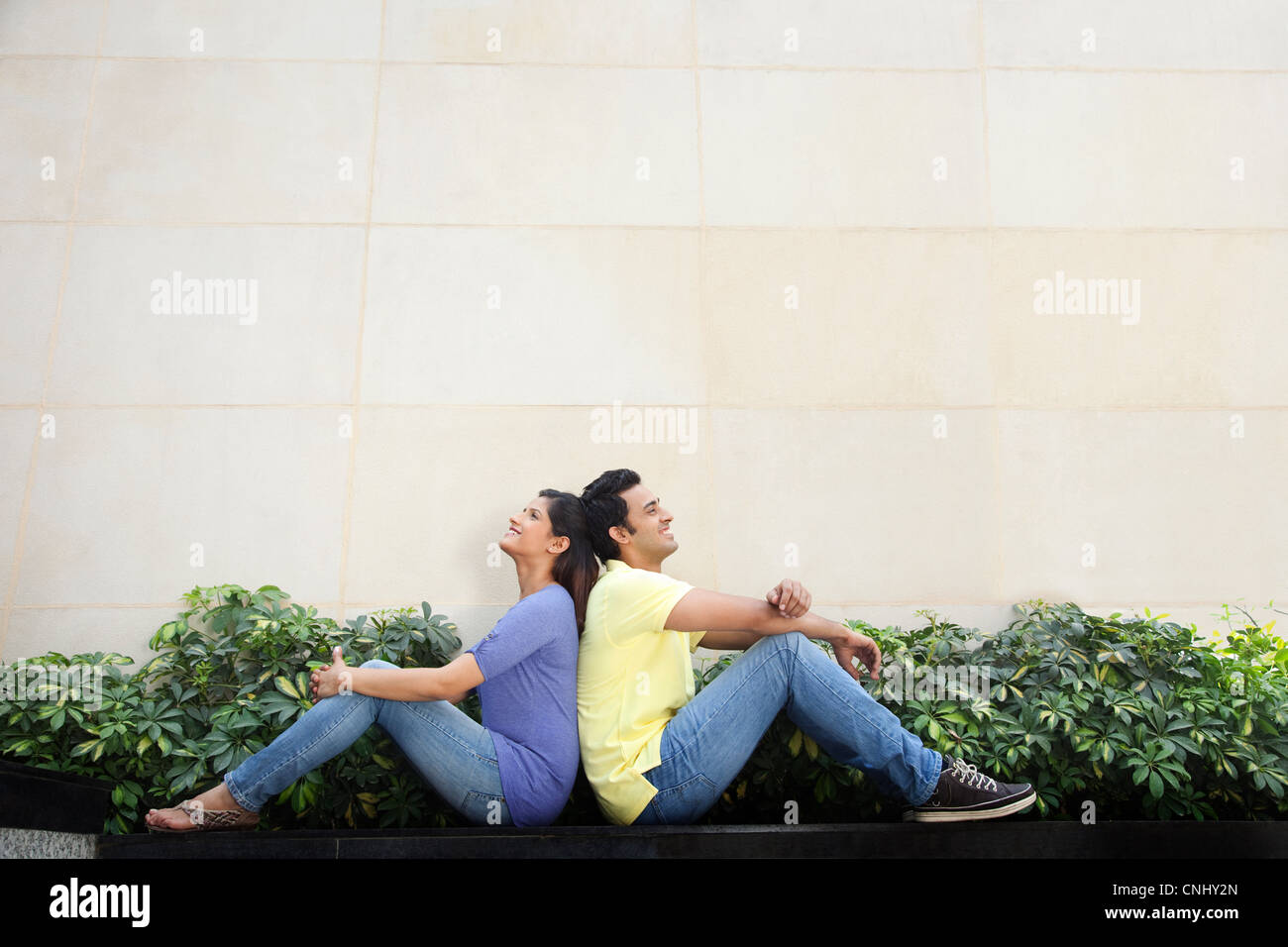 Couple sitting back to back - Stock Image