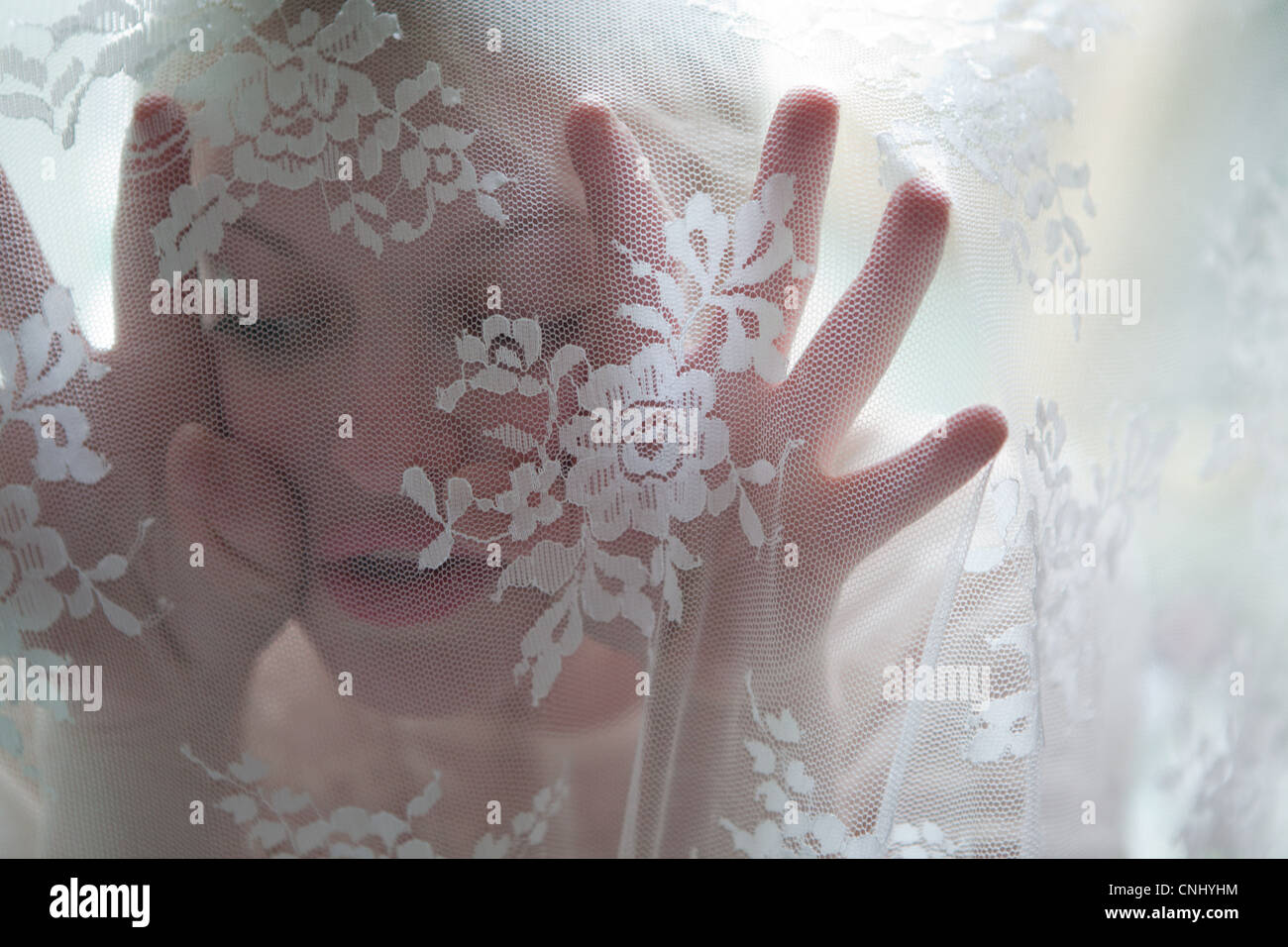 Young woman behind lace curtain - Stock Image