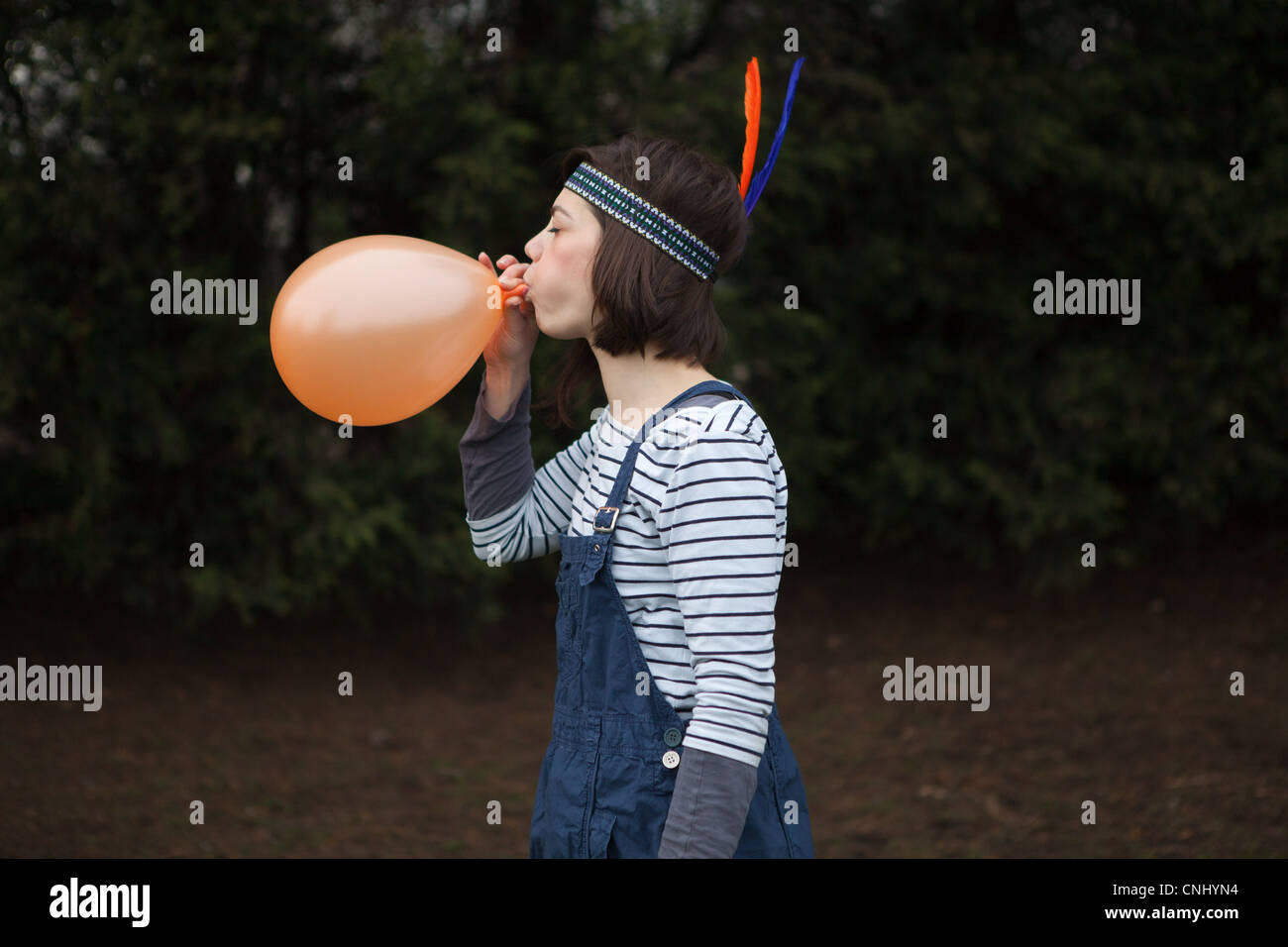 Young woman in headdress, blowing up a balloon - Stock Image