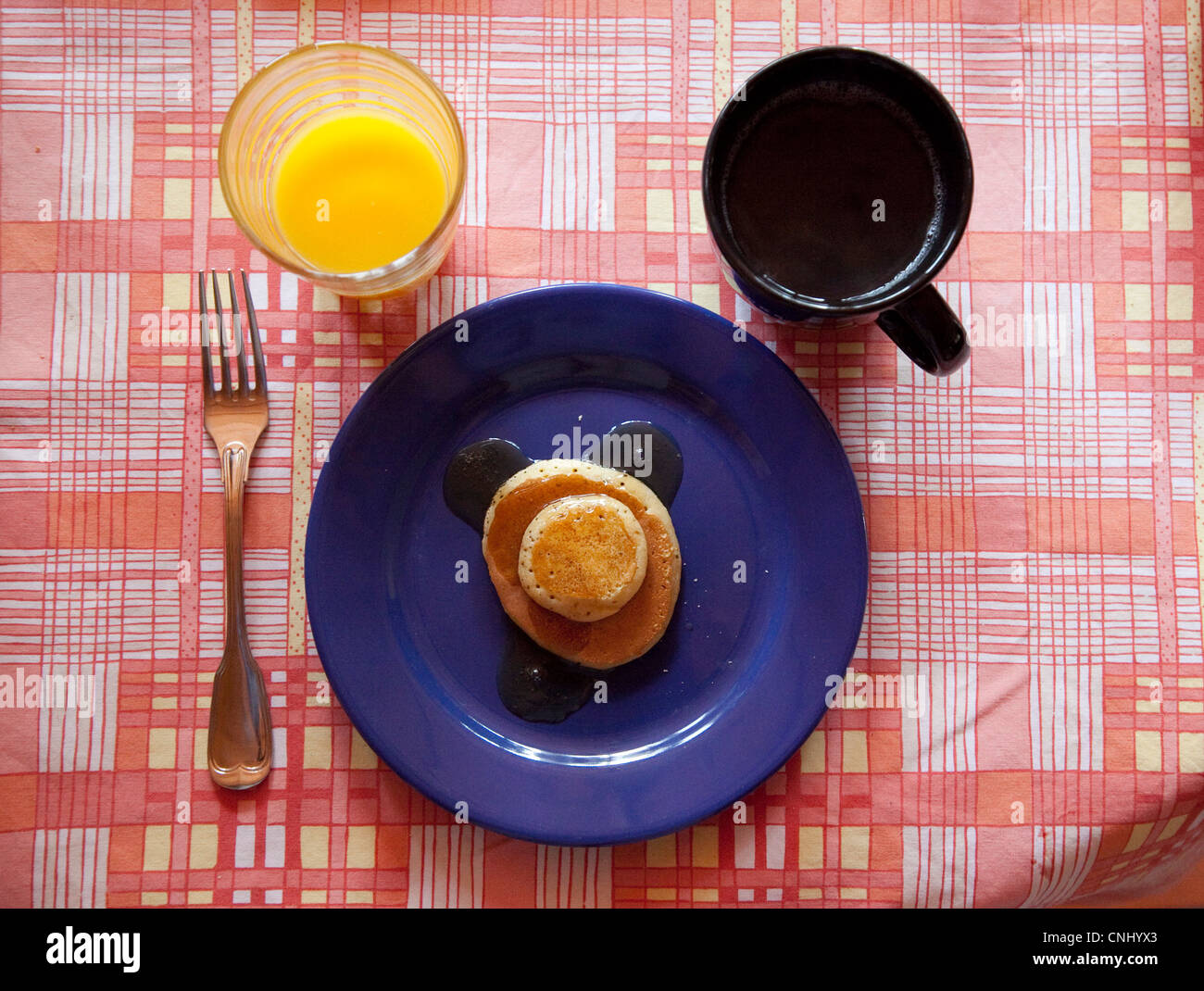 A colour image of a breakfast setting Pancakes, tea and orange juice. - Stock Image