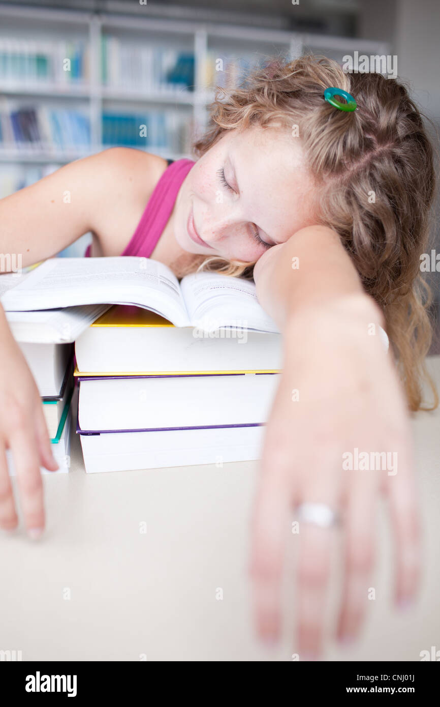 pretty female tired/exhausted/sleepy college student taking a nap in a library (shallow DOF; color toned image) - Stock Image