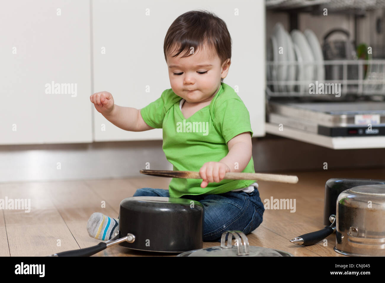 Baby playing with pots and pans - Stock Image