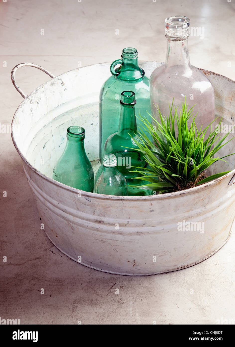 Bottles and plant in an old tub - Stock Image
