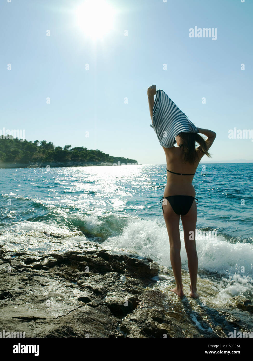 Young woman taking off t-shirt by the sea - Stock Image