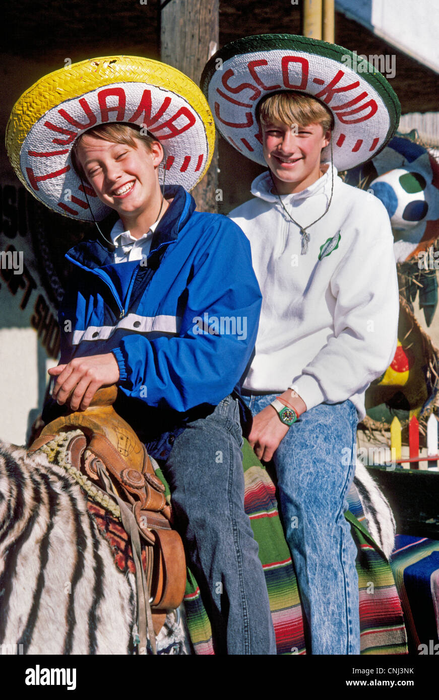 Two smiling American boys mount a donkey striped like a zebra to pose for  photos in silly Mexican sombrero hats during their visit to Tijuana c9d469763ed