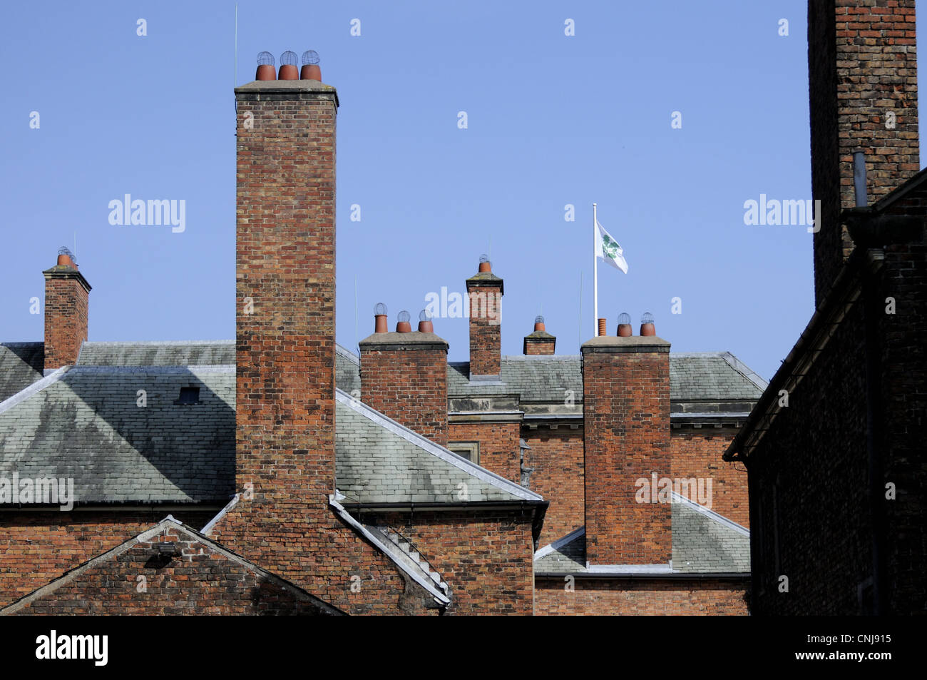 Chimney stacks at Dunham Massey with National Trust flag flying behind them - Stock Image