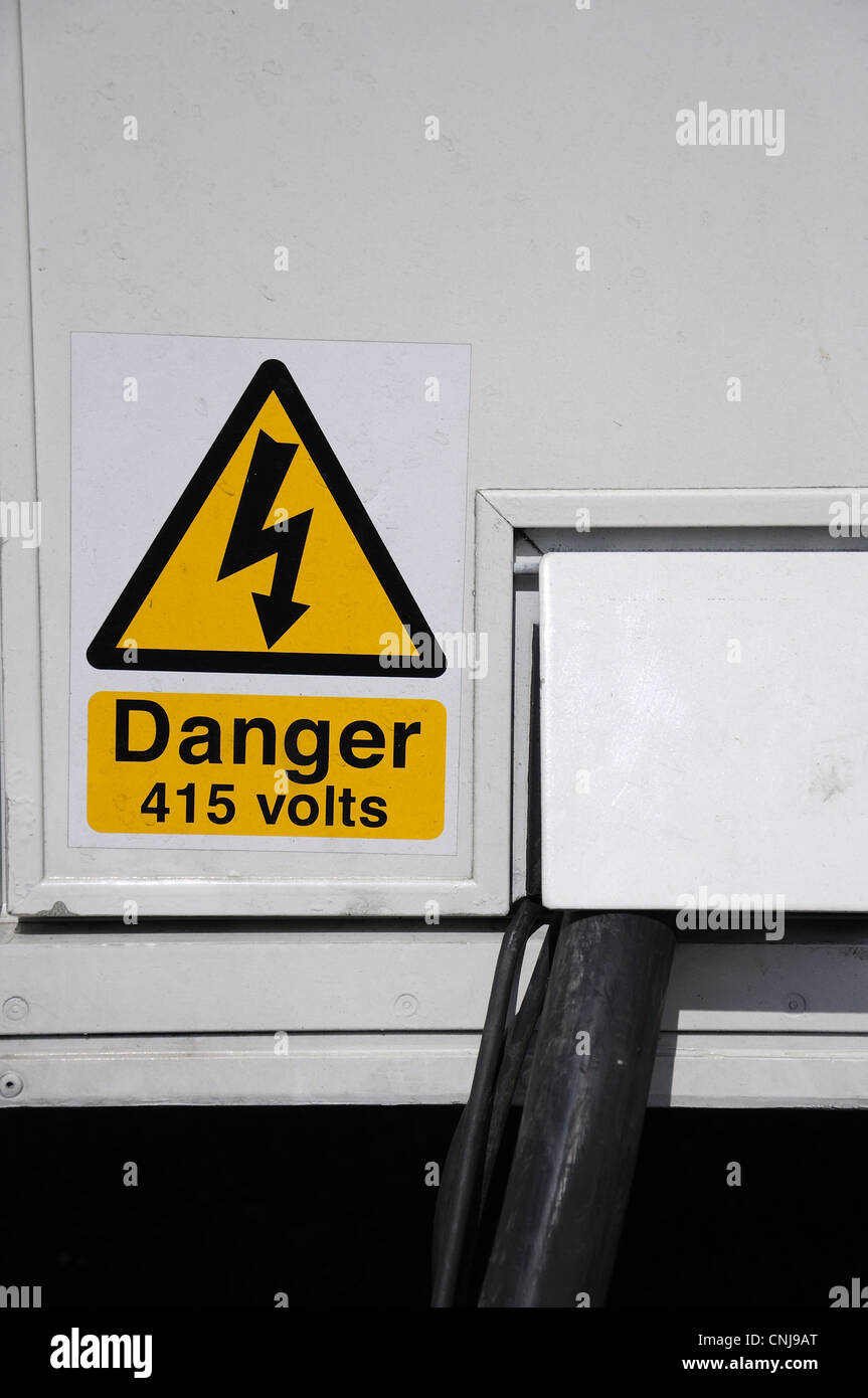 Yellow electrical hazard warning sign by plugged in electric cable - Stock Image