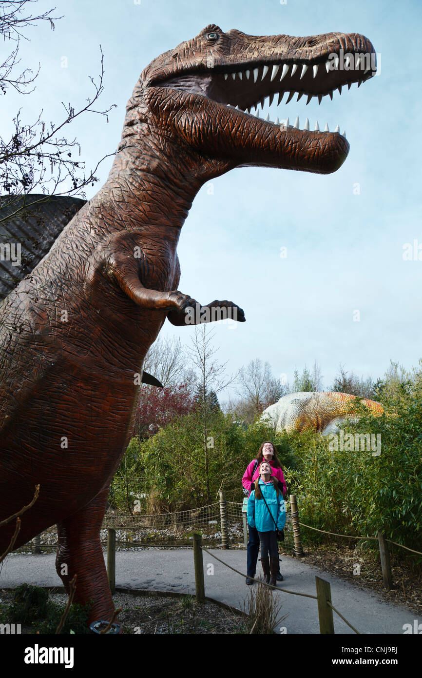 Visitors dwarfed by a model Spinosaurus in the Dinosaur Safari at Blackpool Zoo. - Stock Image