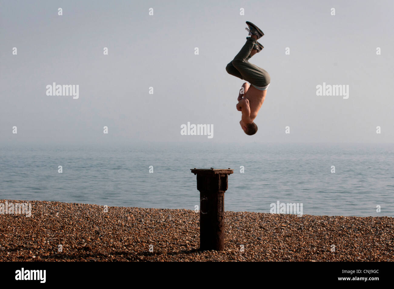 An acrobat somersaults on Brighton beach in England - Stock Image