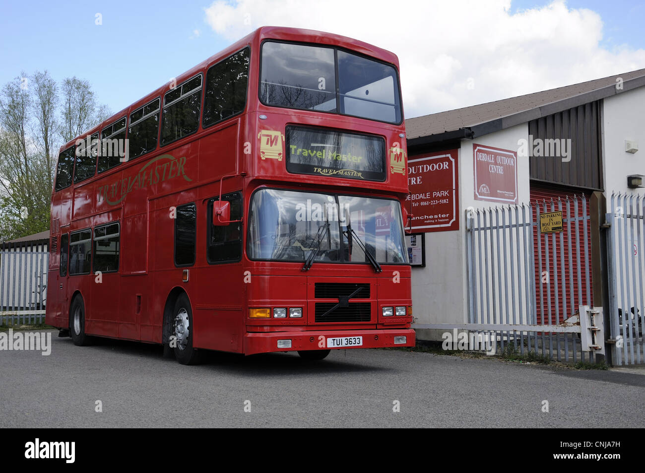 Red double decker Travelmaster bus parked outside Debdale Outdoor Centre in Gorton. - Stock Image