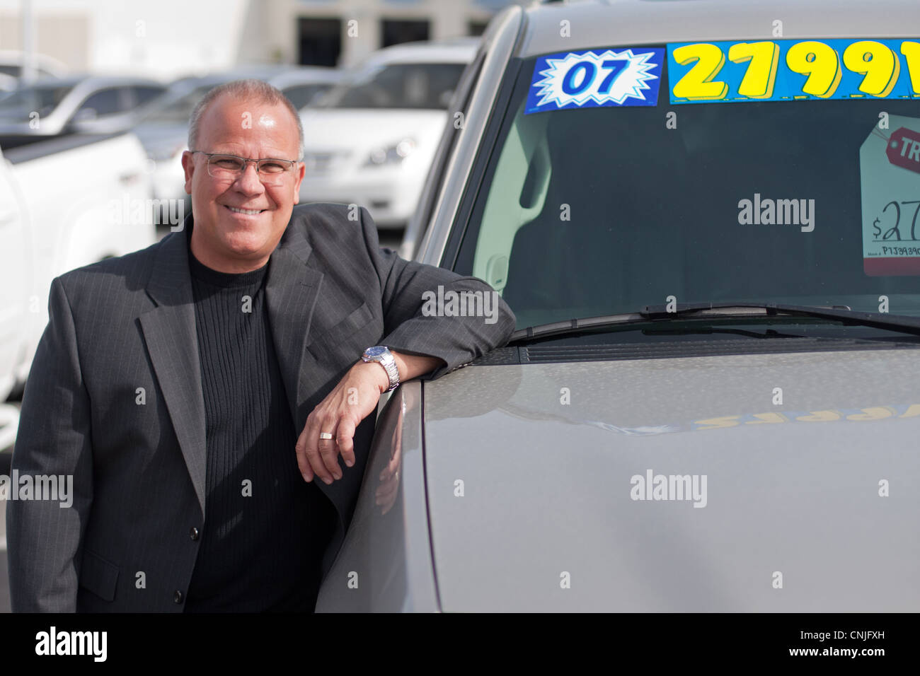 car salesman on lot with price sticker on car selling - Stock Image