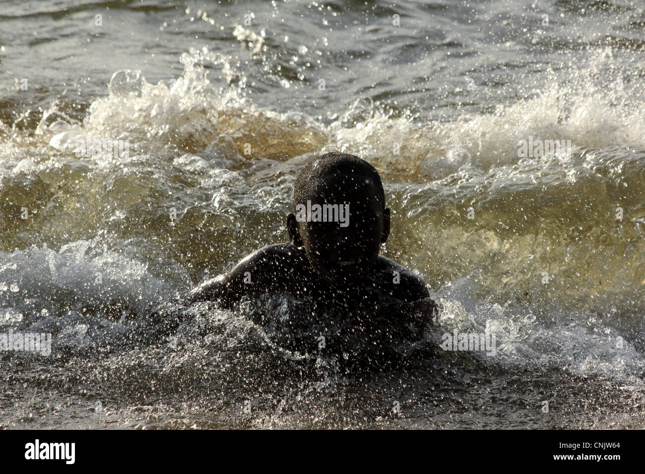 Boy bathing and playing at the shore of Victoria lake, Musoma, northern Tanzánie - Stock Image