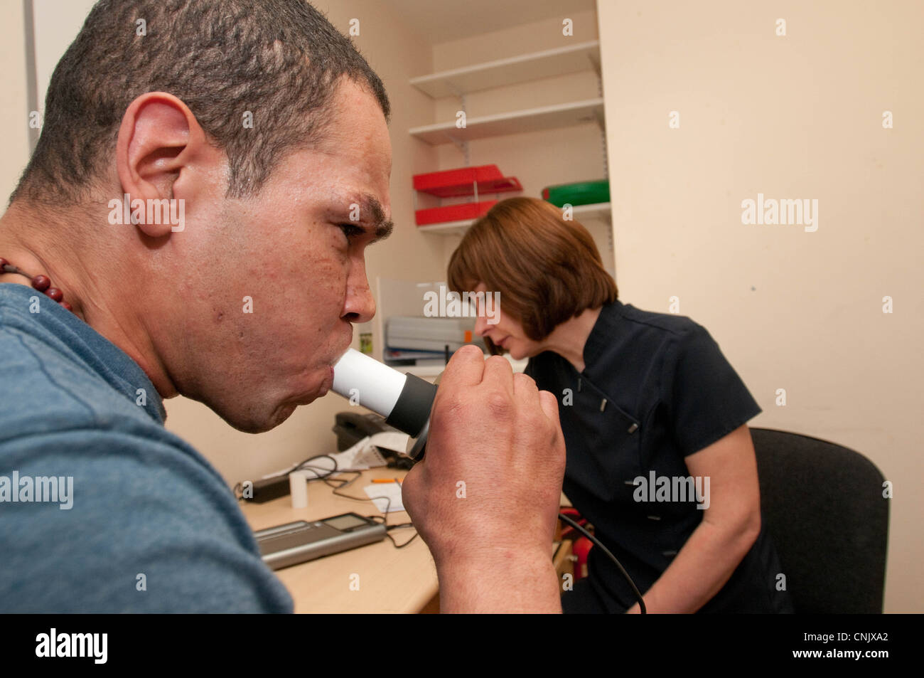 Homeless man having his lung capacity measured as part of an assessment for TB - Stock Image