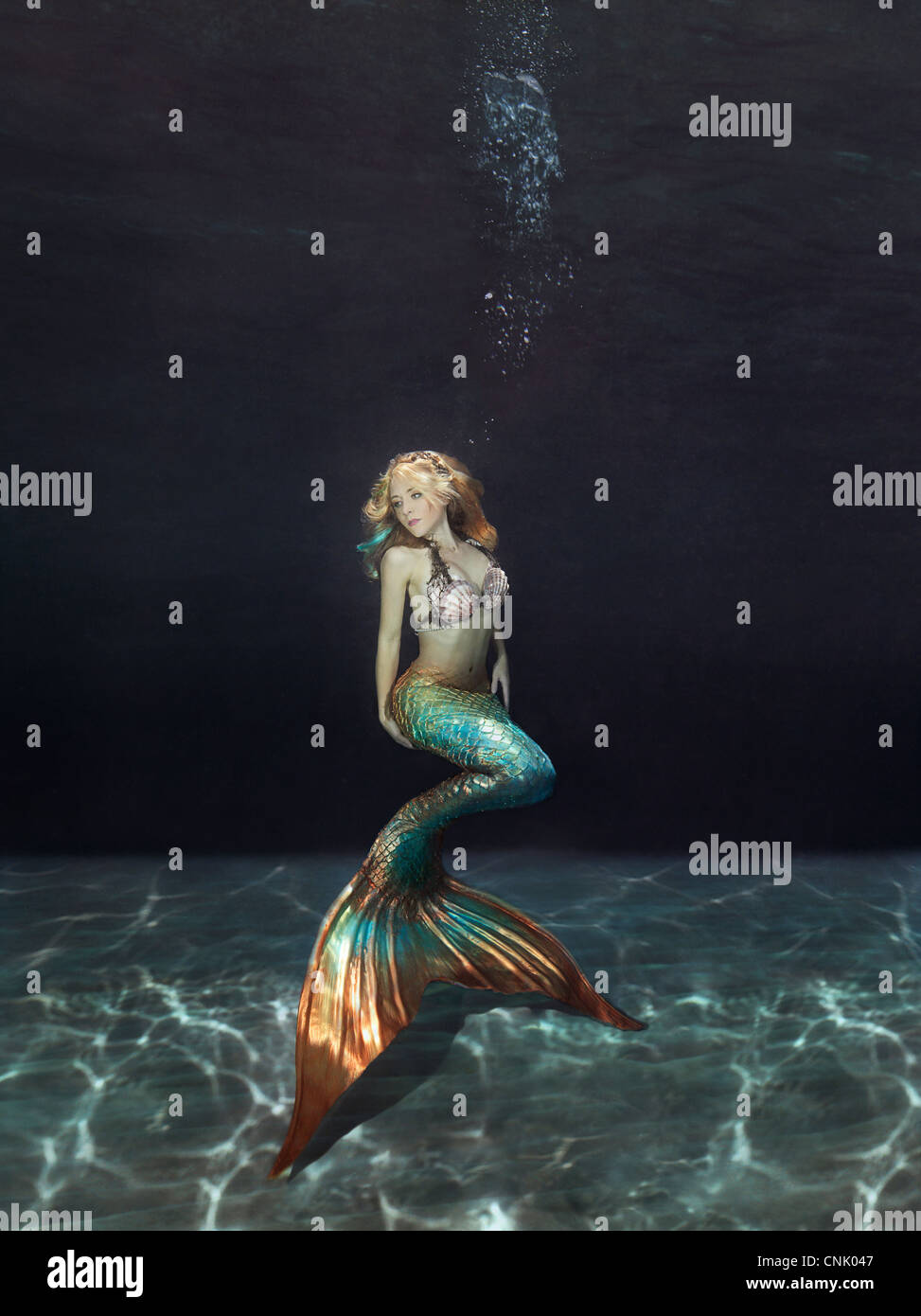 Mermaid underwater floating above the sandy bottom - Stock Image
