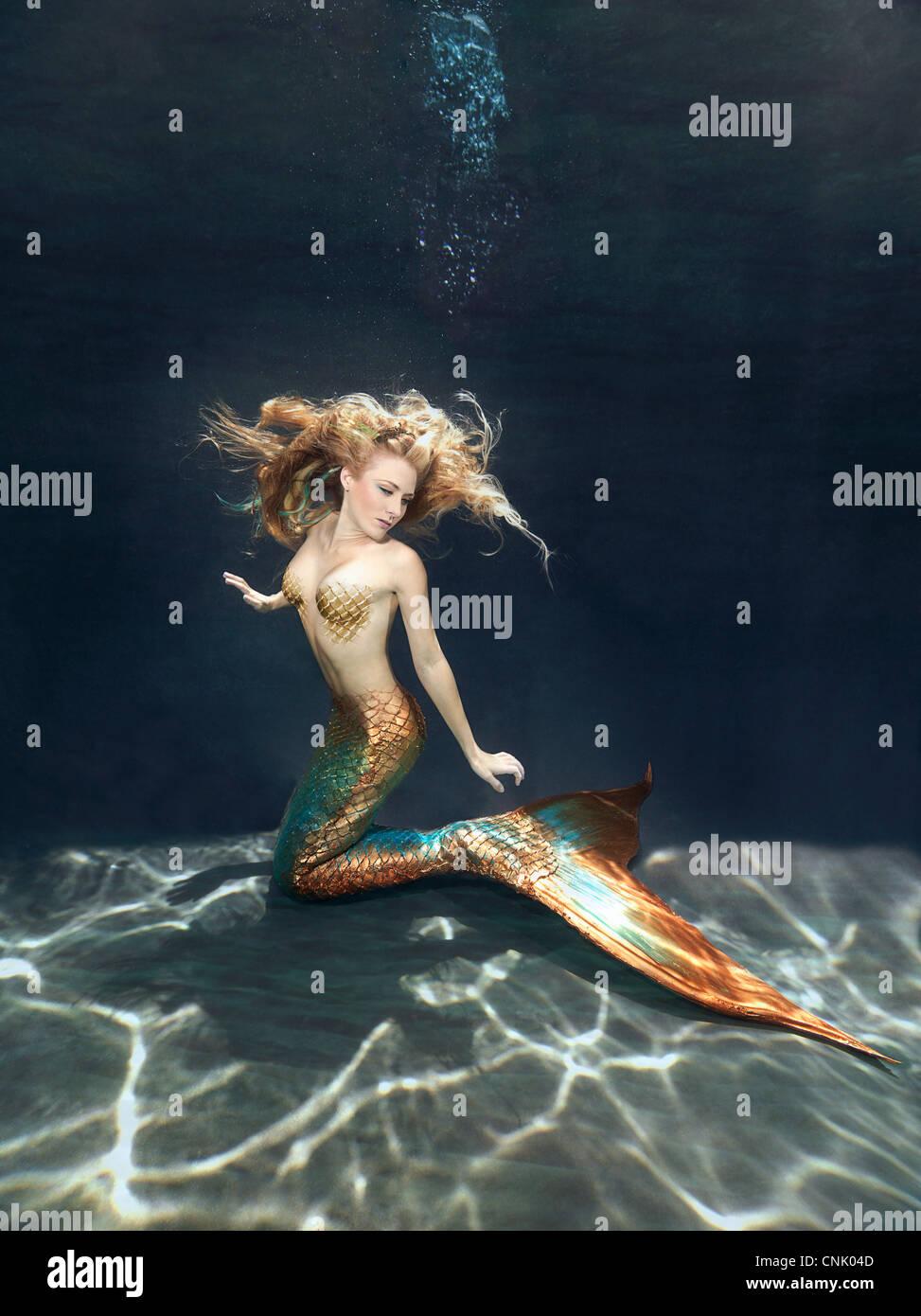 Mermaid underwater kneeling on the sandy bottom of the sea, reaching for her fluke Stock Photo