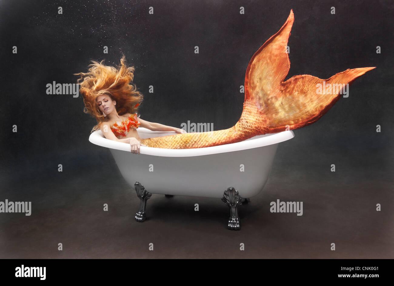 Young mermaid lounging underwater in her Victoria + Albert bathtub - Stock Image