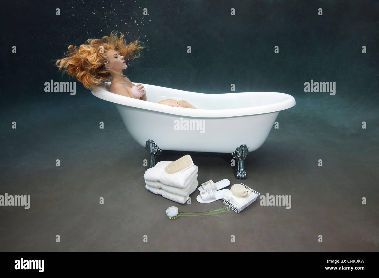 Young woman bathing herself underwater in her Victoria + Albert clawfoot bathtub - Stock Image