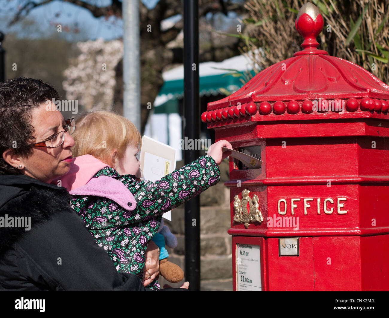 Mother and daughter posting letters in traditional post box - Stock Image