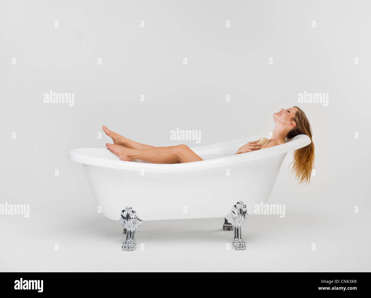 Young woman bathing herself in her Victoria + Albert claw foot tub - Stock Image