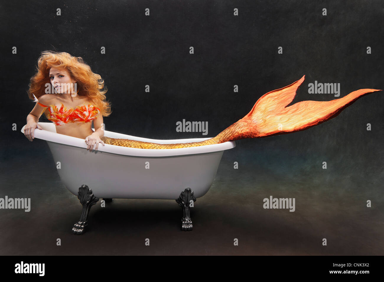 Young mermaid laying underwater in her Victoria + Albert bathtub - Stock Image