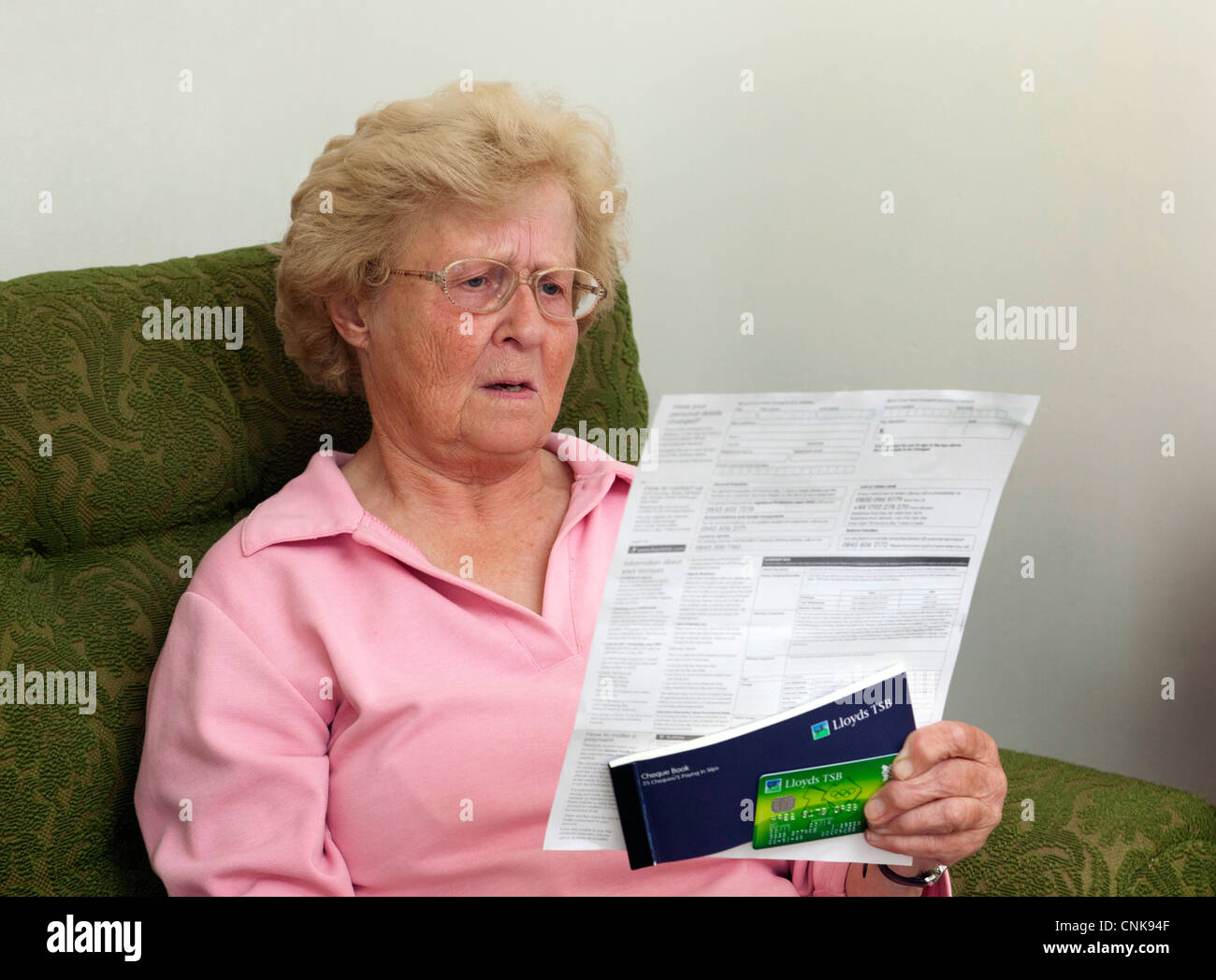 senior woman / pensioner shocked by credit card bill / bank statement - Stock Image