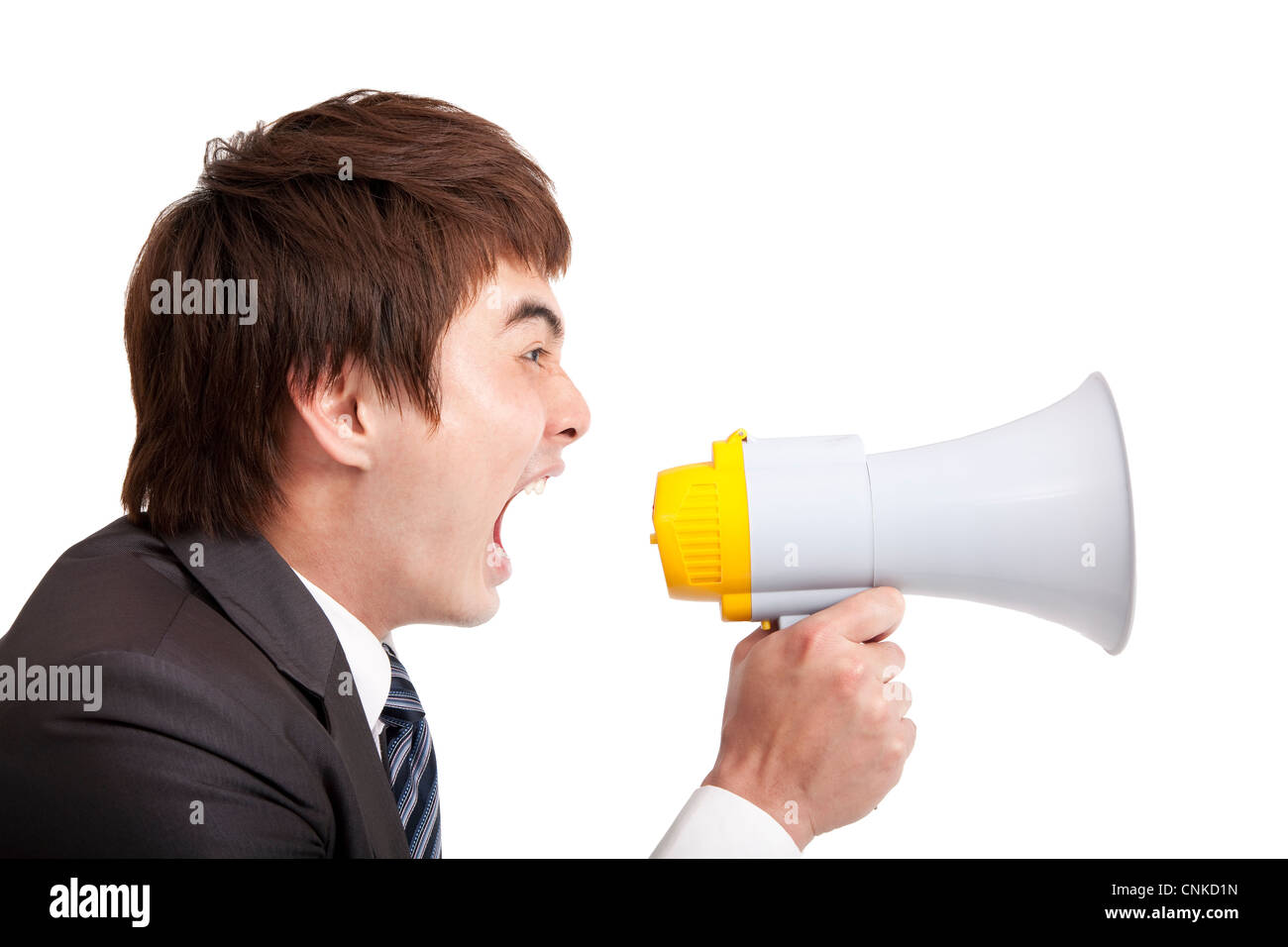 young Businessman screaming by megaphone - Stock Image