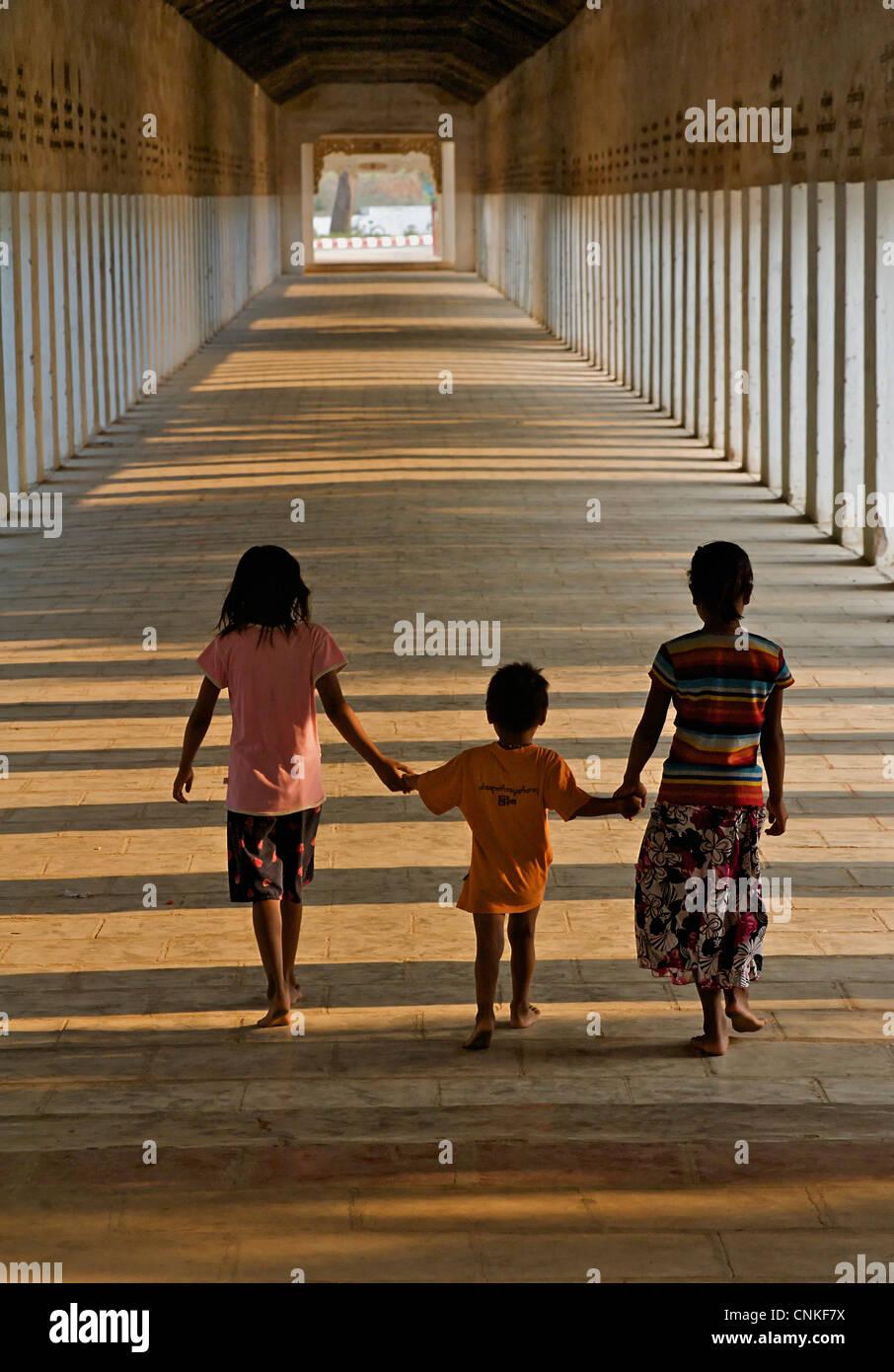 Burmese children walking in the corridor at Shwezigon Pagoda, Bagan. Burma. Myanmar Stock Photo