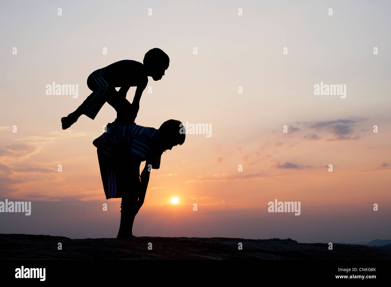 Silhouette of young Indian boys playing leap frog against at sunset. India - Stock Image