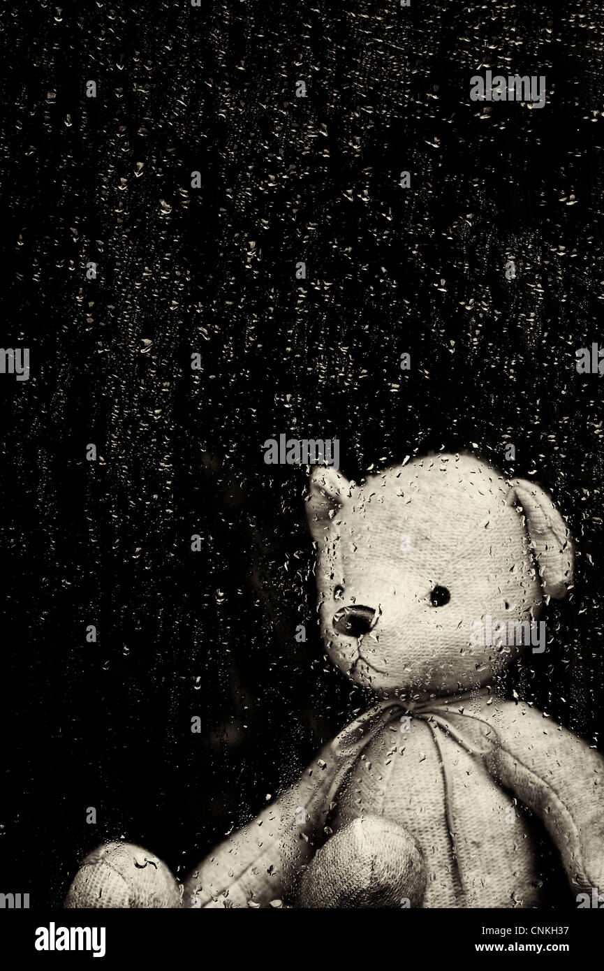 Sad Teddy bear looking through a window covered in rain drops. Sepia Toned. Still life - Stock Image