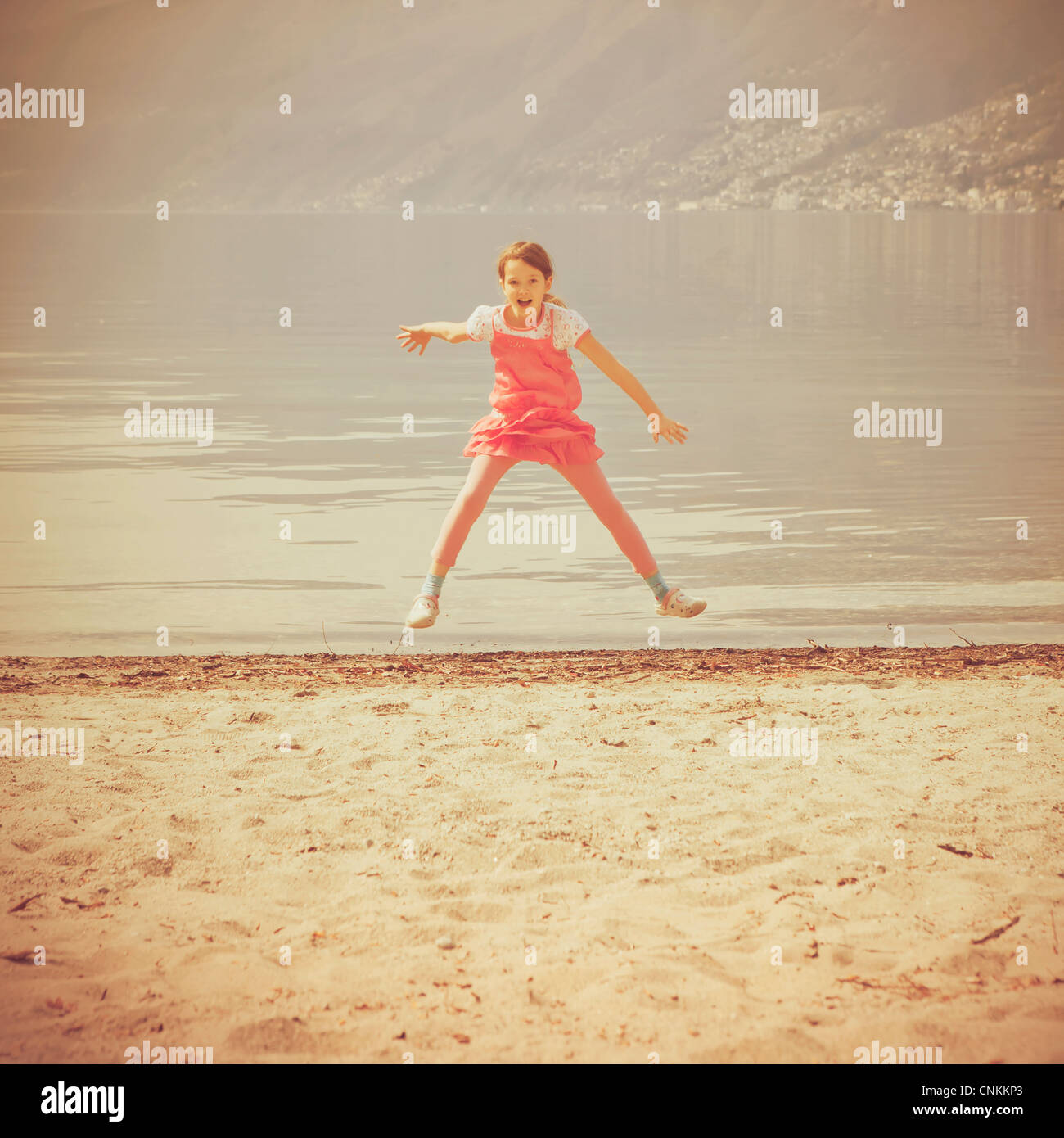 girl jumps in the air on a beach - Stock Image