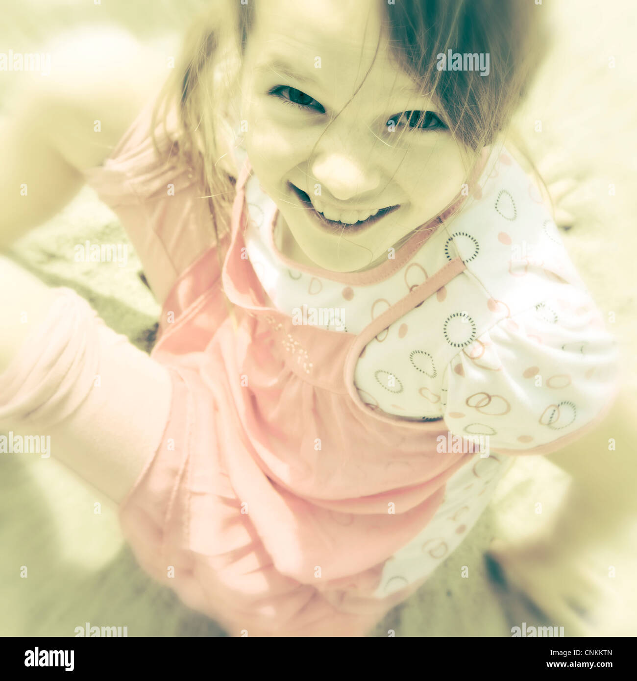 young girl sitting on the beach, photographed from above - Stock Image