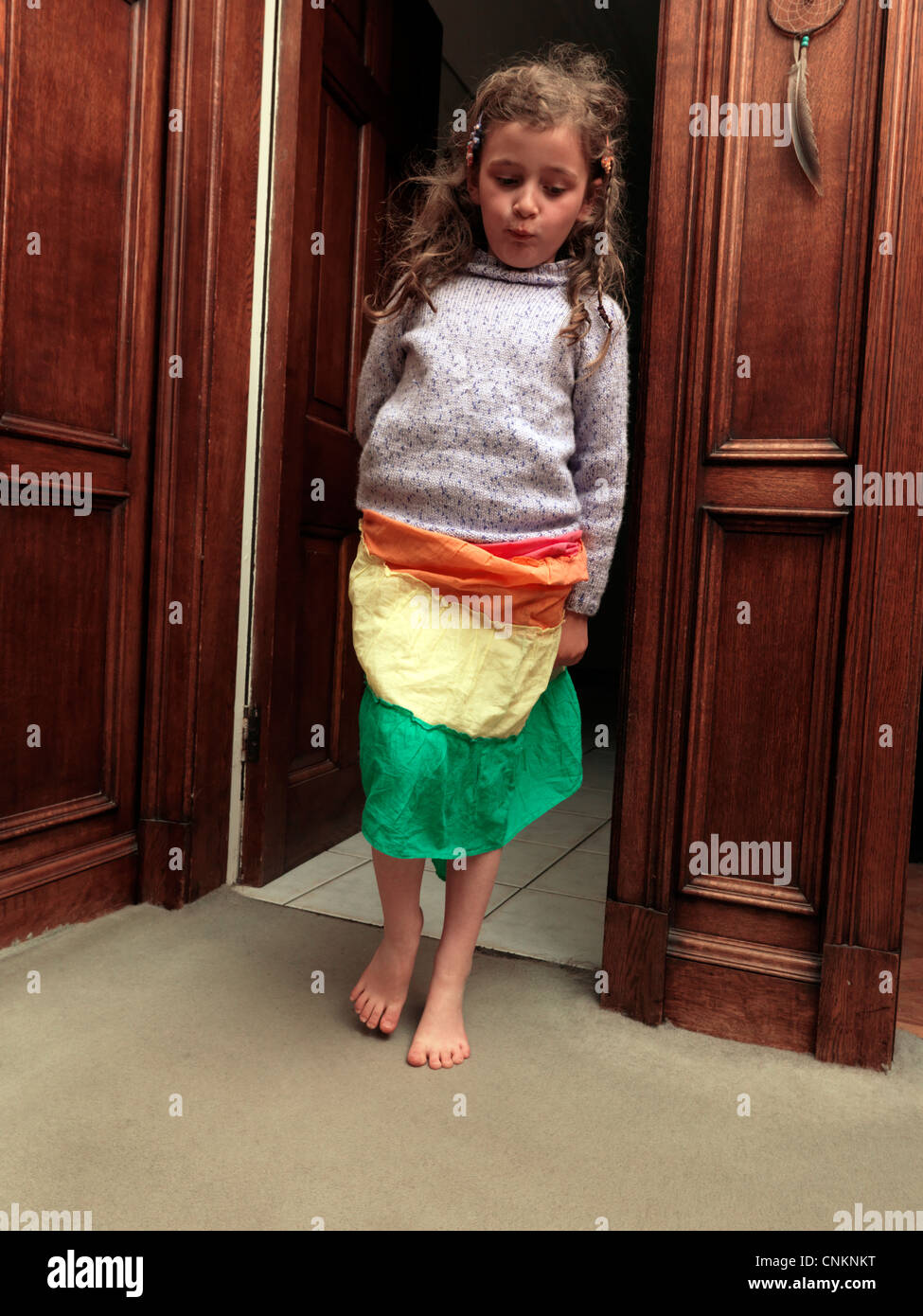 Young Girl Tip Toeing Through Doorway England - Stock Image