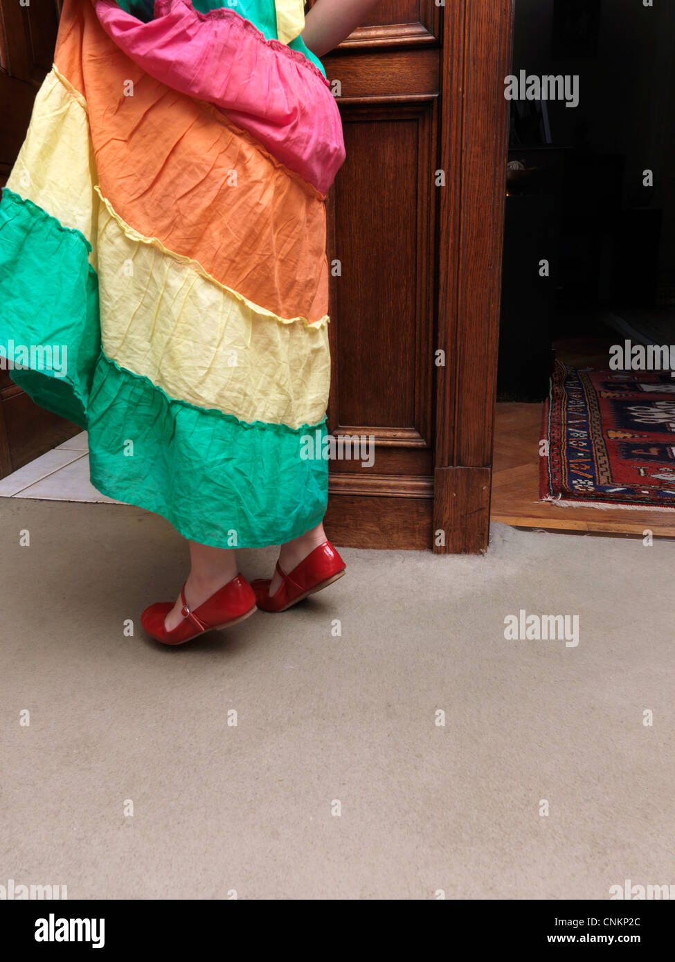 Young Girl Tip Toeing In Red Shoes Through Doorway England - Stock Image