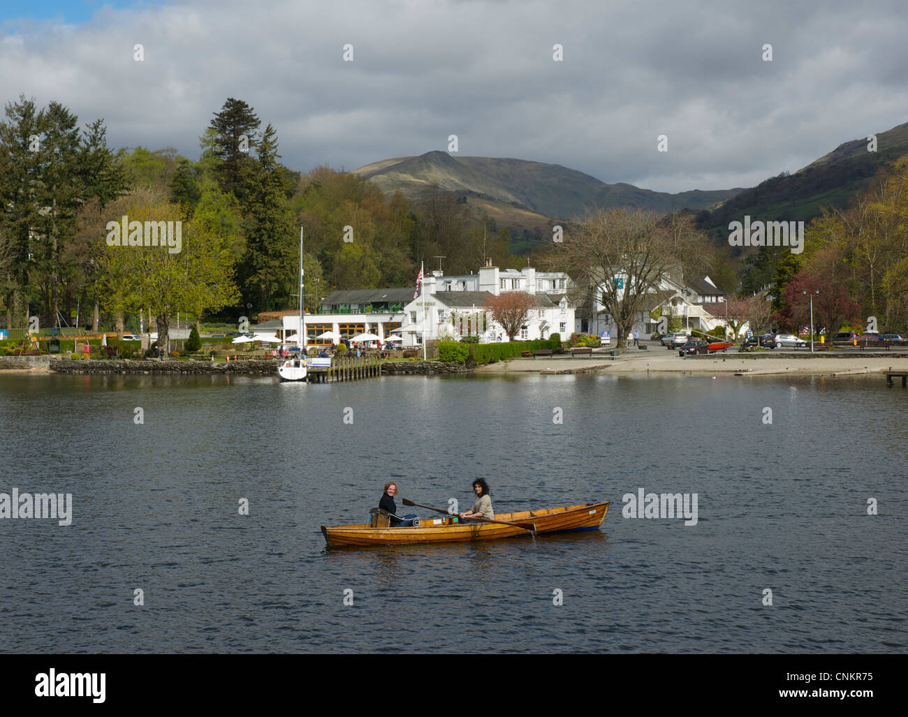 Two young women in a rowing boat on Lake Windermere, at Waterhead, Lake District National Park, Cumbria, England - Stock Image