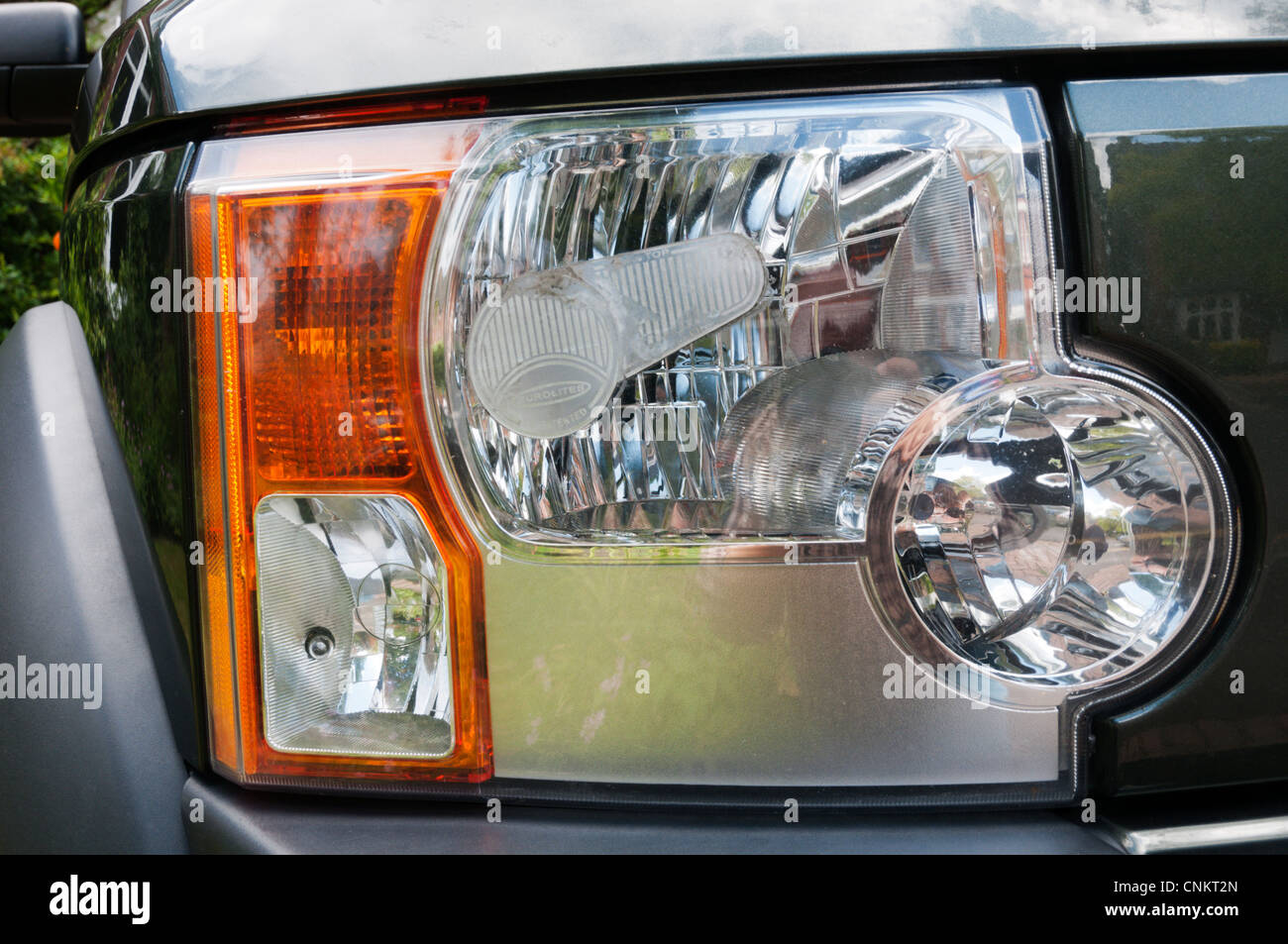 Beam deflector fitted to offside headlight of a Land Rover Discovery 3, for driving on the right-hand side of the - Stock Image