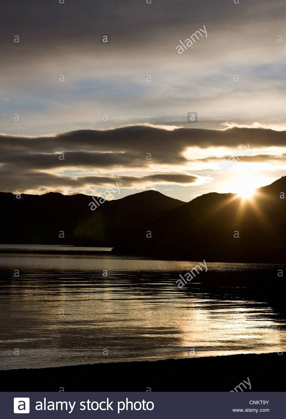 Sun setting over mountain range - Stock Image