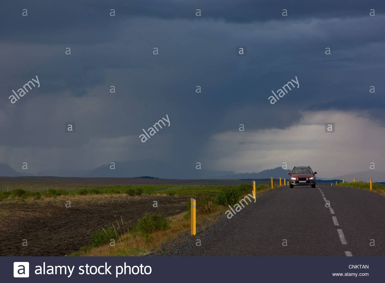 Car on rural road under dramatic sky - Stock Image