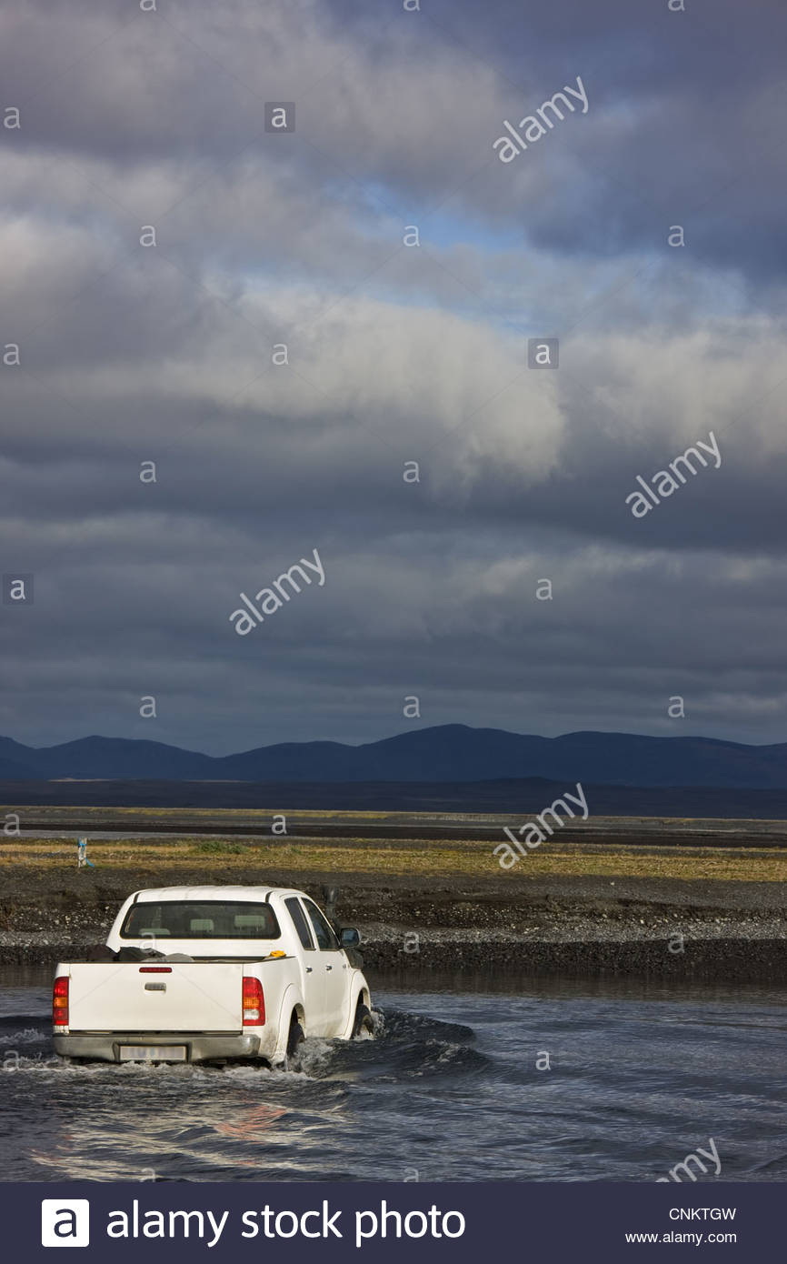 Truck driving through river - Stock Image