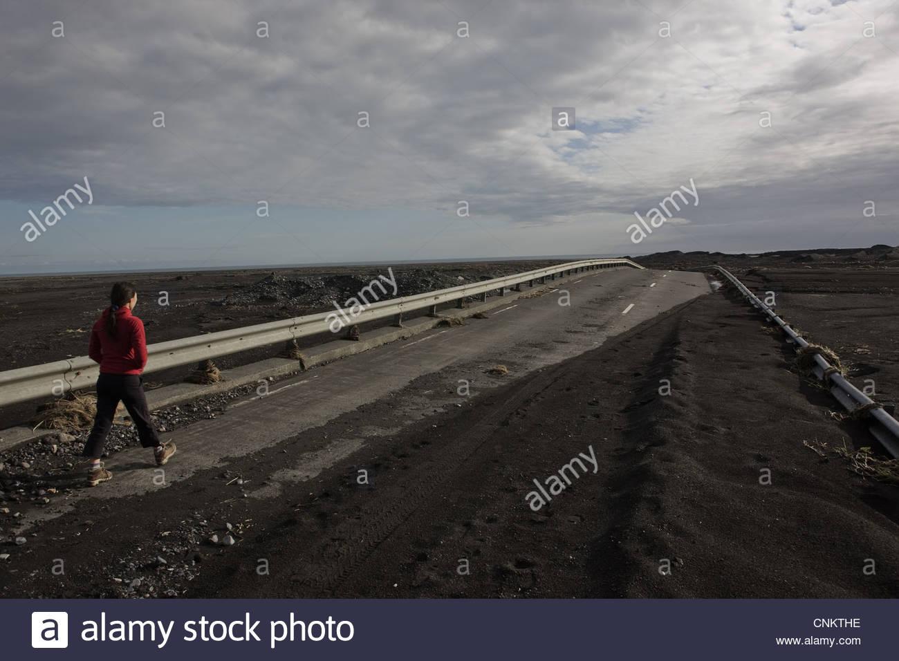 Woman walking on rural road - Stock Image
