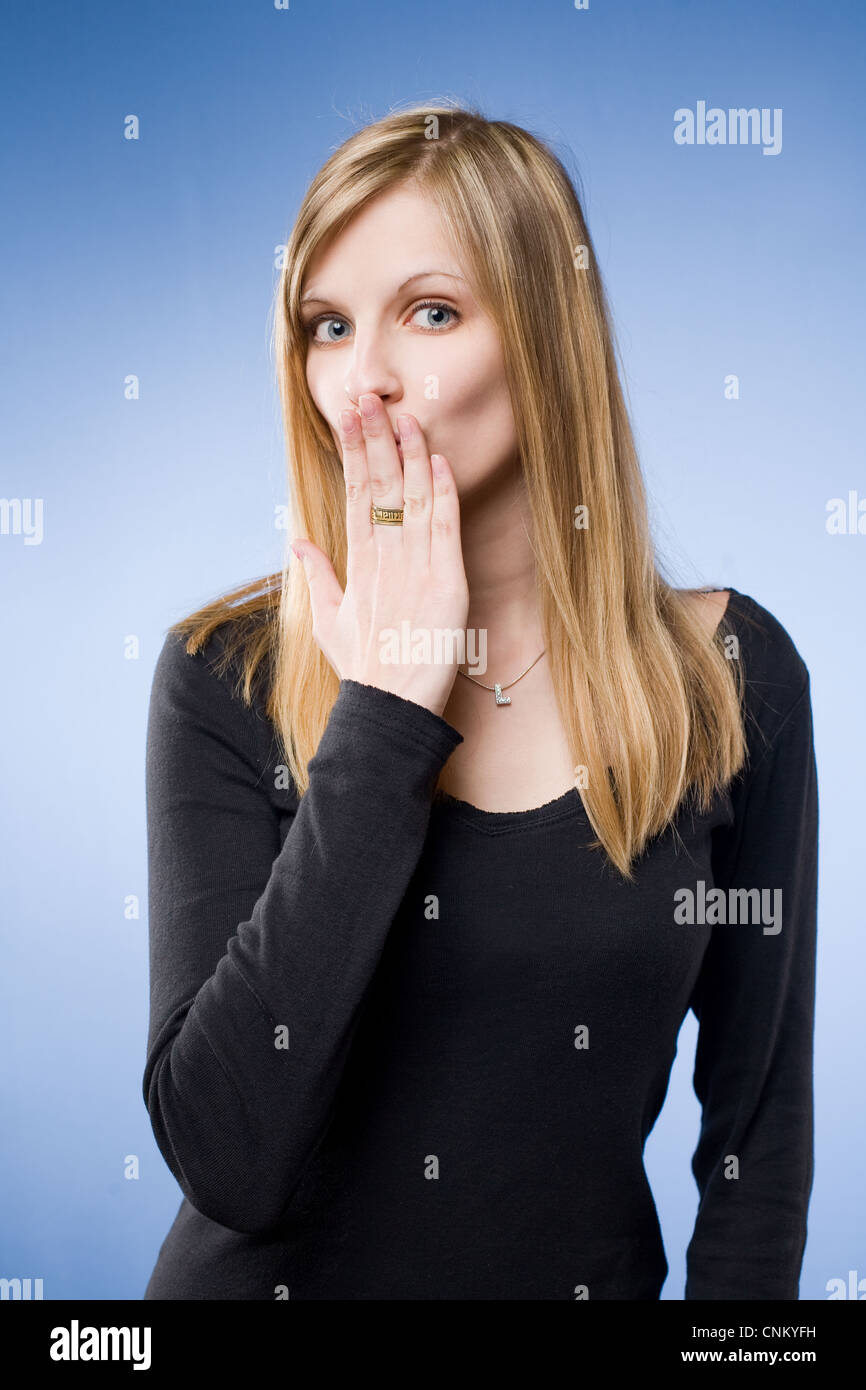 The big surpirse, portrait of a shocked looking beautiful young blond woman. - Stock Image