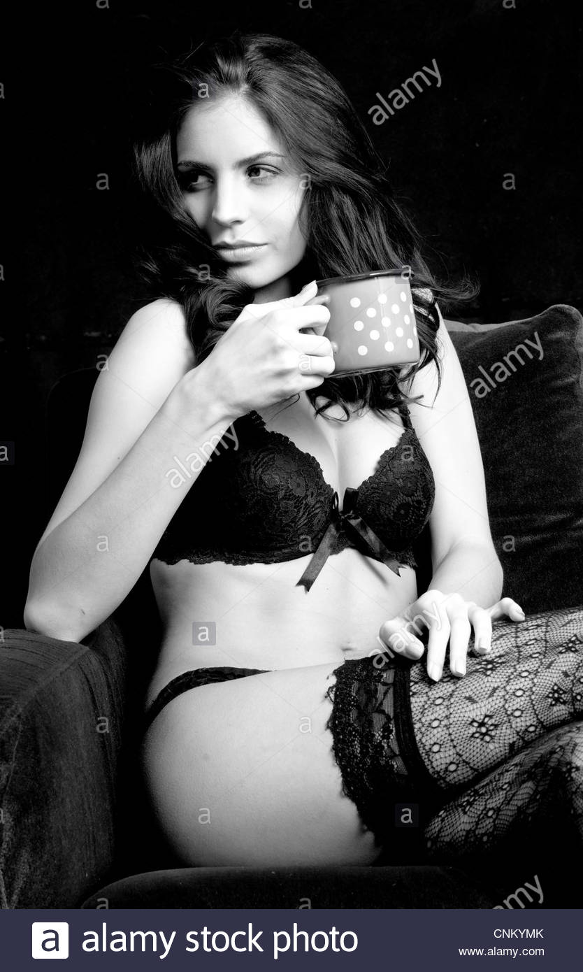 e3a50c33fc55 Young woman drinking a cup of coffee holding a mug brunette sit sitting  armchair wearing stockings lingerie couch sofa